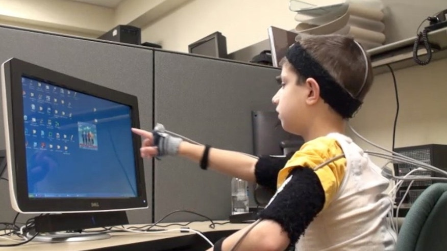 A nonverbal child with autism successfully points to a computer screen while wearing motion capture technology.