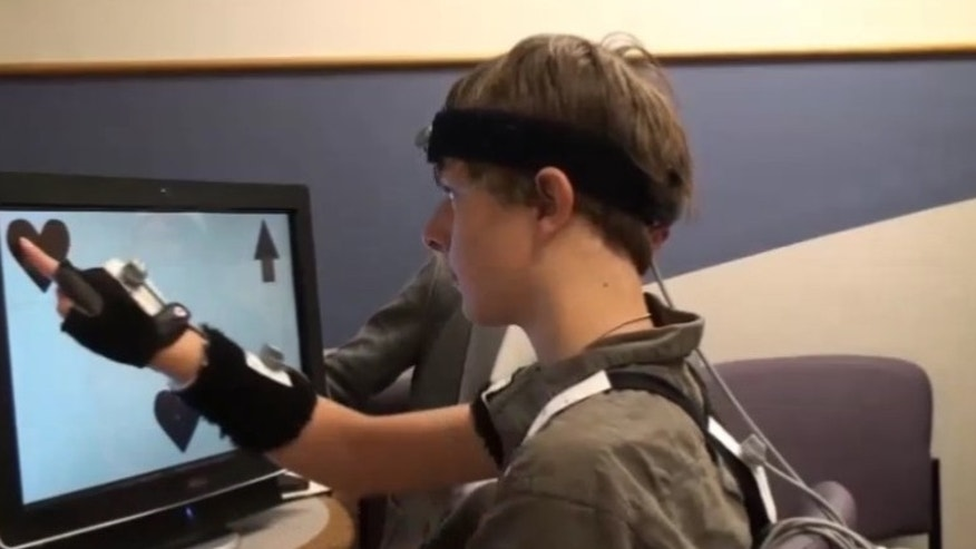 A child with autism successfully matches two geometric shapes on a computer screen while wearing motion capture technology.