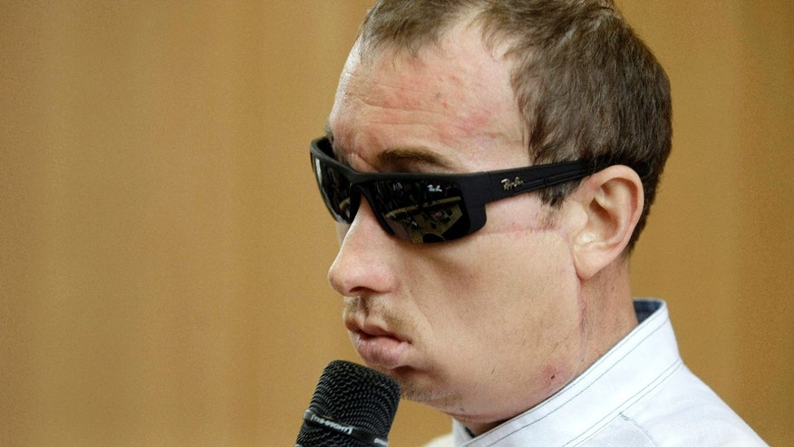 Poland's first face transplant patient, identified only by his first name Grzegorz, speaks at a press conference after he was discharged from the hospital.