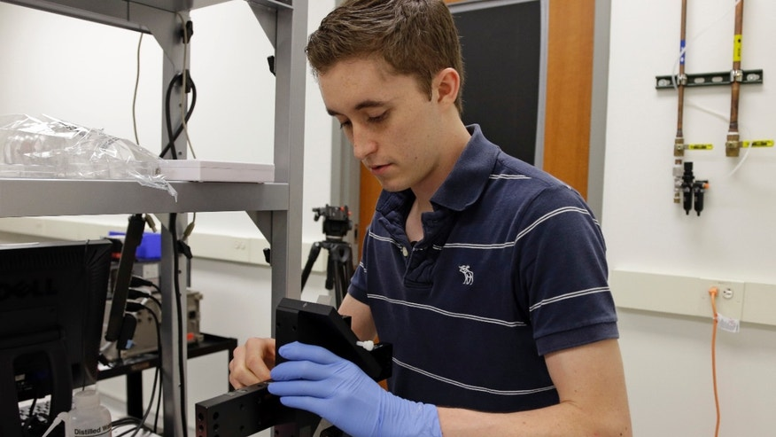 Kenny Long, a graduate researcher studying engineering and medicine at the University of Illinois, Urbana-Champaign works with a handheld biosensor based on an iPhone.