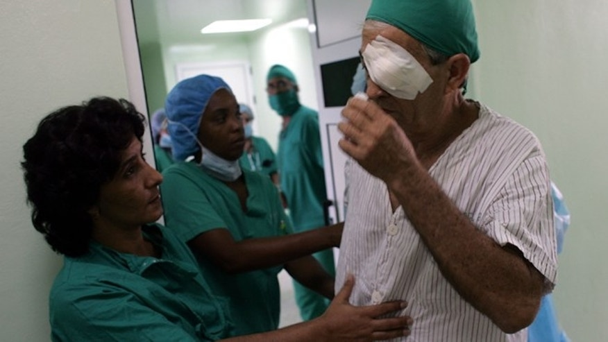 "HAVANA - SEPTEMBER 12:  Doctors help a patient after he had eye surgery performed by doctors participating in ""Operacion Milagro"" (Operation Miracle) September 12, 2006 at Pando Ferrer hospital in Havana, Cuba. The program is a joint health care program setup between Cuba and Venezuela which offers free eye care in Cuban hospitals for people living in Latin America and the Caribbean.  (Photo by Joe Raedle/Getty Images)"