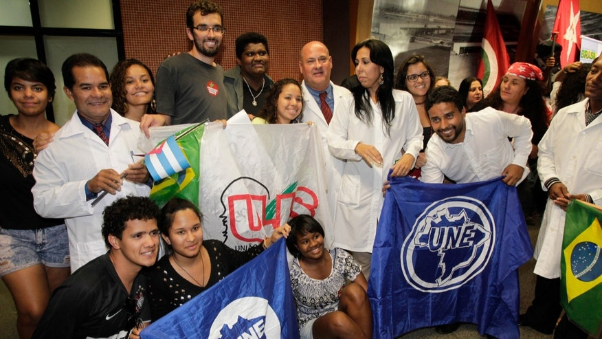 Cuban doctors pose for a photo with Brazilian students after their arrival at the International airport, in Brasilia, Brazil, Saturday, Aug. 24, 2013. More than 200 Cuban doctors have arrived in Brazil to work in impoverished areas where physicians and medical services are scarce in Latin America's biggest country, the Health Ministry said Saturday. (AP Photo/Eraldo Peres)