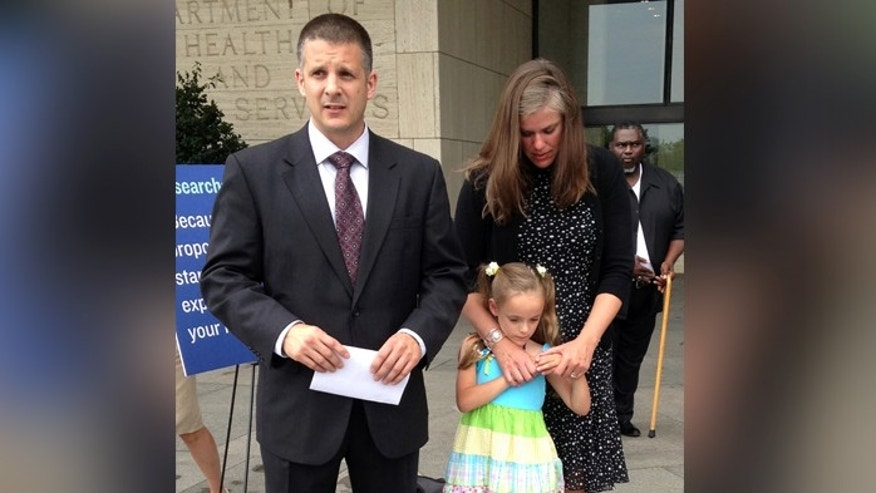 Shawn and Carrie Pratt of Kingwood, W.Va., with their daughter Dagen, speak to the media outside a federal health meeting in Washington. Dagen was part of a controversial study of premature babies that has sparked questions about how to inform patients about the risks of medical research.