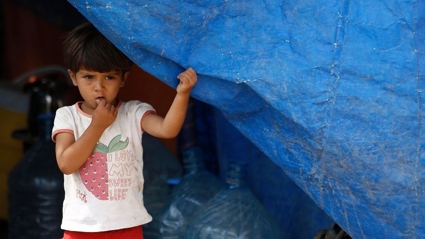 A Syrian refugee girl looks from a tent at the Domiz refugee camp in the northern Iraqi province of Dohuk. The number of Syrian children forced to flee their devastated homeland reached 1 million on August 23, 2013.