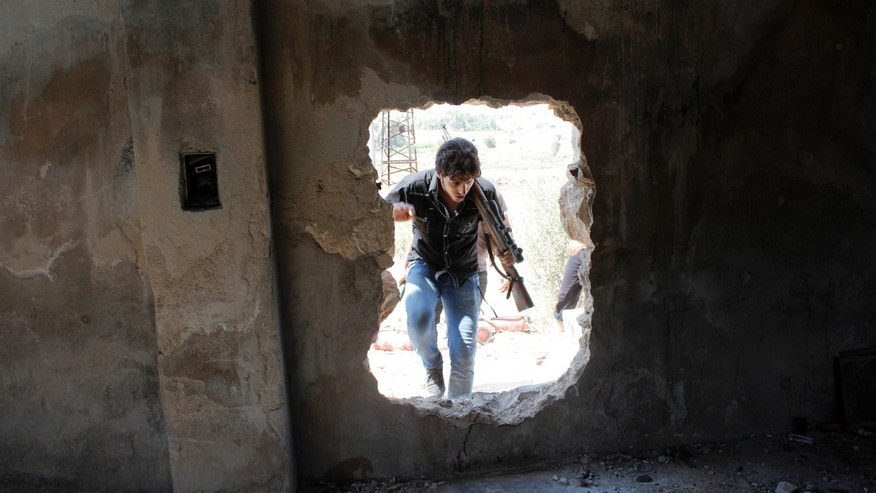 A Free Syrian Army fighter walks through a hole in a wall beside the Canadian Hospital in Aleppo, August 31, 2013. (REUTERS/Molhem Barakat)