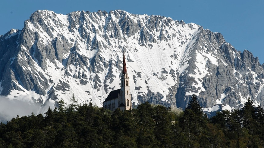 A chapel is seen in front of the snow covered Karwendel mountains on a sunny spring day in the western Austrian village of Silz. (REUTERS/ Dominic Ebenbichler)