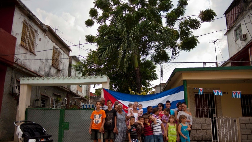 Pairs of twins pose for a group portrait near a Siguaraya tree along their street in Havana, Cuba.