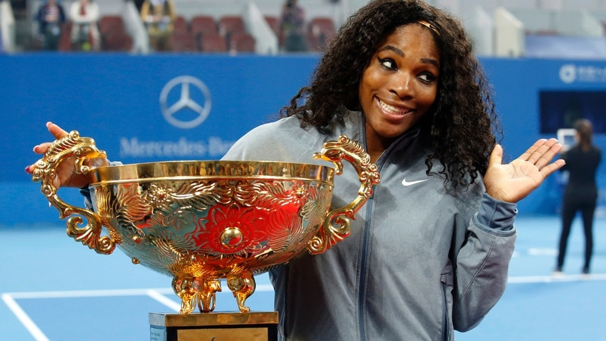 Serena Williams poses with her trophy after winning her women's singles final match against Jelena Jankovic of Serbia at the China Open tennis tournament in Beijing.