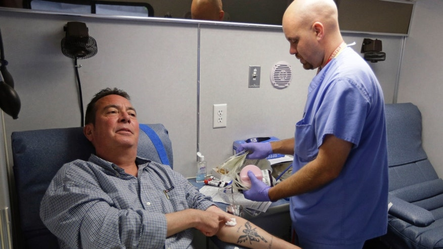 Technician Greg Snyder, right, finishes up a blood draw from Chris Page after he donated blood in an Indiana Blood Center Bloodmobile in Indianapolis. The Indiana Blood Center announced in June 2013 that it would reduce its mobile operations, close a donor center and cutting other costs because demand from hospitals had fallen 24 percent from the previous year.