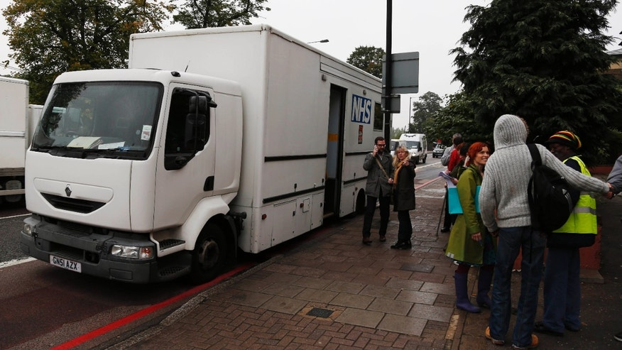 Medical staff and volunteers wait for homeless people as they arrive to have their X-rays taken, at a van, parked outside their homeless shelter, in London.