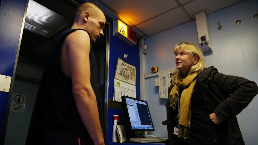 Homeless Danny Hastie, 20, listens to radiographer Diana Taubman, right, explain the findings of his X-ray, that came negative for tuberculosis, at a van in London.