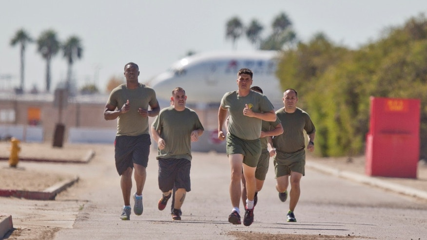 "A group of sailors and Marines who failed the so-called ""tape test"" are led by an instructor on a three mile run as they work to improve their fitness and remain in the military, at the Marine Corps Recruit Depot in San Diego. (AP Photo/Lenny Ignelzi)"