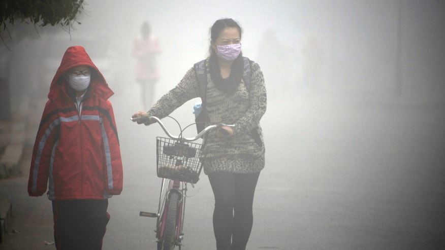 People walk along a street during a smoggy day in Jilin, Jilin province, October 22, 2013.  (REUTERS/Stringer)