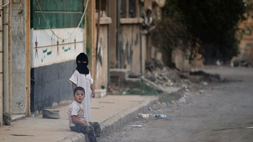 A child wears a mask as he stands along a street in Deir al-Zor, eastern Syria, October 3, 2013. Ten children from Deir al-Zor have been diagnosed with polio, according to WHO. (REUTERS/Khalil Ashawi)