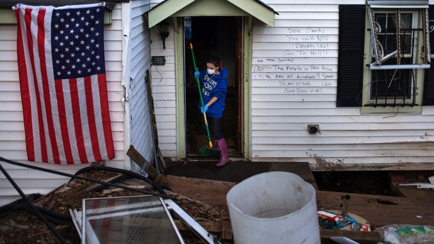 A 13-year-old cleans her flooded home in the Staten Island borough of New York on November 4, 2012. One year later, some Sandy survivors are experiencing respiratory problems as a result of exposure to mold and other environmental toxins in the aftermath of the storm. (REUTERS/Adrees Latif)