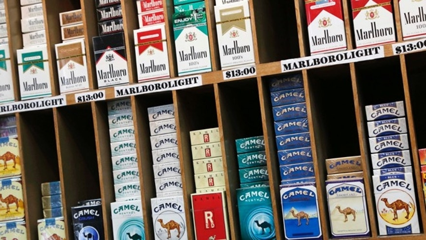 FILE- In this March 18, 2013 file photo, cigarette packs are displayed at a convenience store in New York. On Wednesday, Oct. 30, 2013, law makers in New York City voted to raise the cigarette-buying age from 18 to 21. (AP Photo/Mark Lennihan, File)