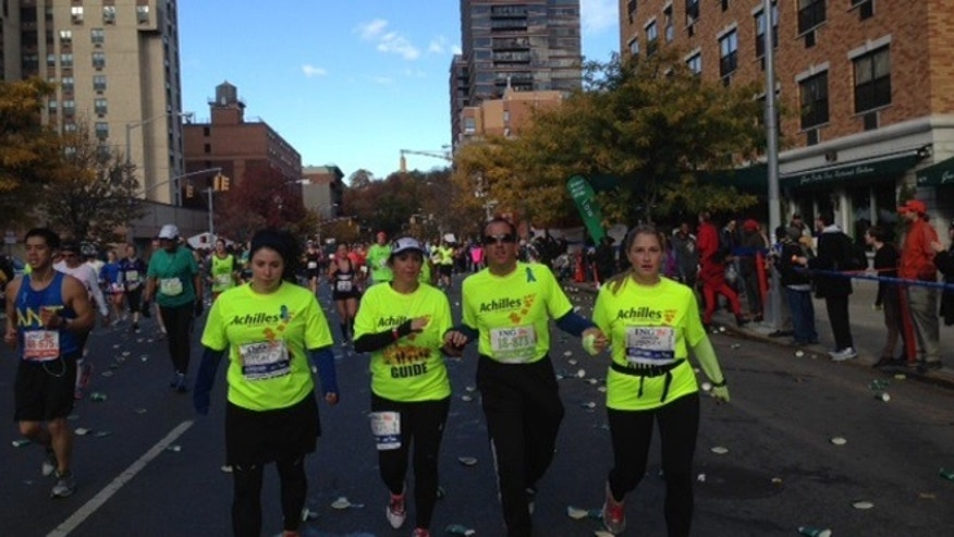 Richard Bernstein running the New York City marathon on Sunday, November 3, accompanied by guides from Achilles International.