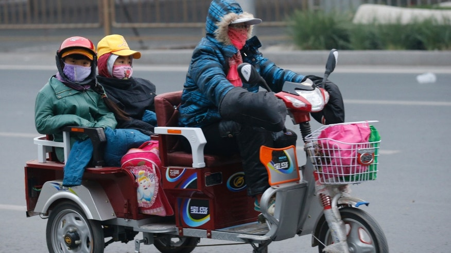 A woman and her children wearing masks ride a vehicle during a smoggy day in Beijing October 28, 2013. (REUTERS/Kim Kyung-Hoon)