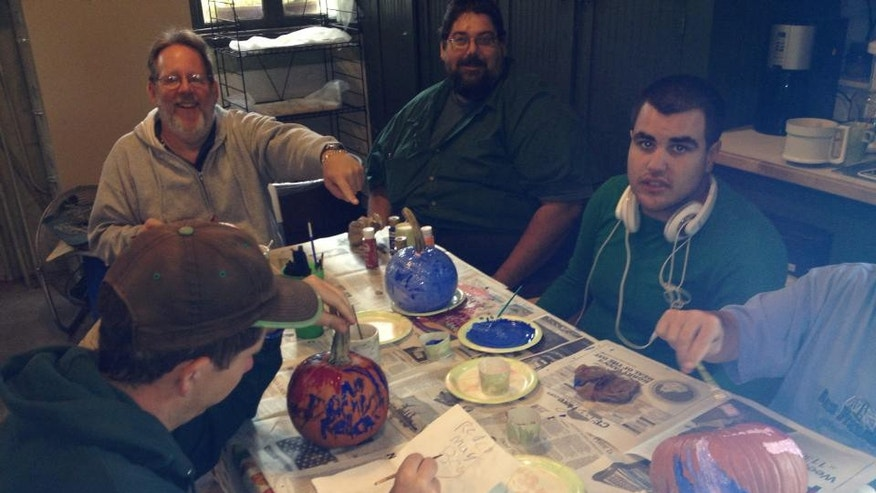 Billy (far right) and others at G.R.O.W.E.R.S. paint pumpkins for Halloween.