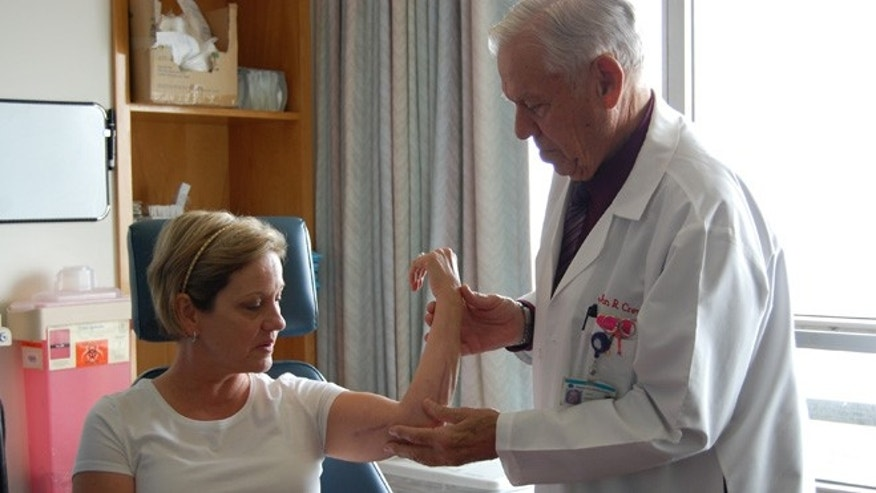 Dr. John Crew, vascular surgeon and wound specialist at Seton Medical Center in Daily City, Calif., examines Lori Madsen's now-healed arm in spring of 2012.