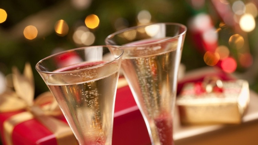 Sparkling Champagne Flutes and Gifts in Front of Decorations and Lights.