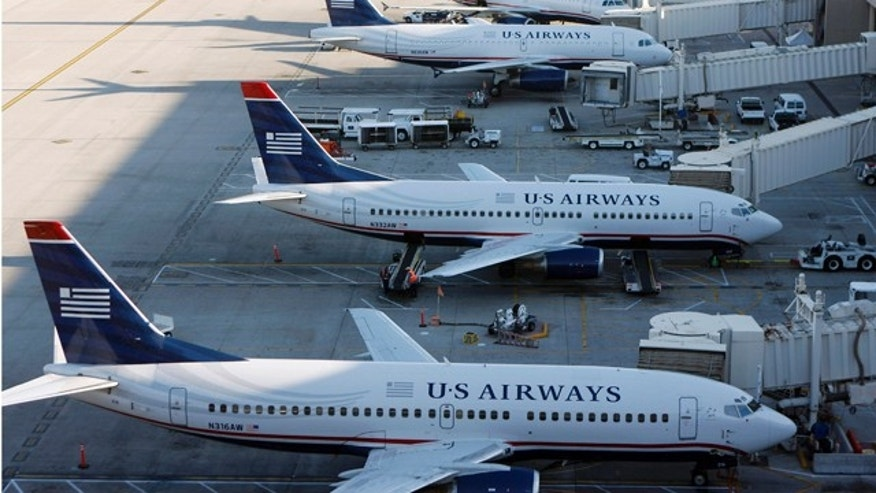 U.S. Airways aircrafts sit outside terminal 4 at Phoenix Sky Harbor International Airport in Phoenix, April 8, 2010. UAL Corp's United Airlines is in merger talks with U.S. Airways in a deal that could create the second-largest carrier in the United States, two sources familiar with the matter said. REUTERS/Joshua Lott (UNITED STATES - Tags: BUSINESS TRANSPORT)