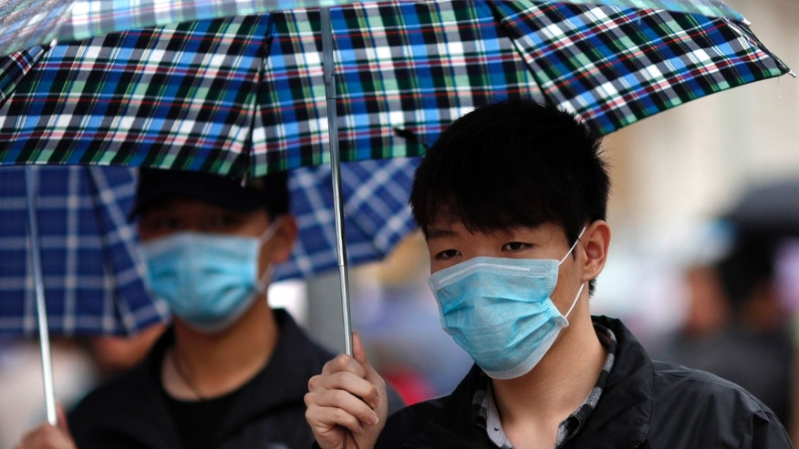 A man wears a face mask as he walks in a shopping area in downtown Shanghai April 5, 2013. REUTERS/Carlos Barria
