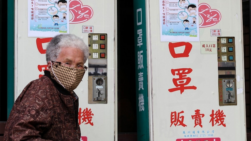A woman wearing a medical mask walks past vending machines that sell masks outside National Taiwan University Hospital in Taipei April 26, 2013. (REUTERS/Pichi Chuang)