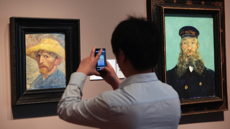 "A visitor at the Detroit Institute of Arts museum uses his cell phone to take a picture of the ""Self Portrait,"" painting by Vincent van Gogh. (REUTERS/Rebecca Cook)"