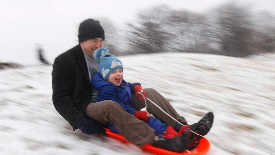 Matt Redmond, 3, and his father, Mike, ride a sled down a hill after an overnight snowfall in Baltimore. (AP Photo/Patrick Semansky, File)