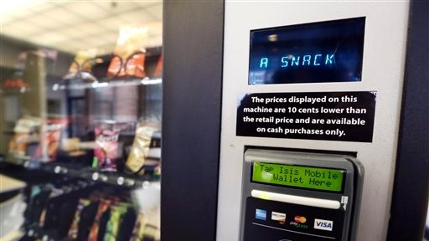 In this Dec. 23, 2013 photo, a vending machine advertises snacks on a small screen on the machine in Seattle. Office workers in search of snacks will be counting calories along with their change under new labeling regulations for vending machines included in President Barack Obama's health care overhaul law. The Food and Drug Administration, which is expected to release final rules early next year, says requiring calorie information to be displayed on roughly 5 million vending machines nationwide will help consumers make healthier choices. (AP Photo/Elaine Thompson)