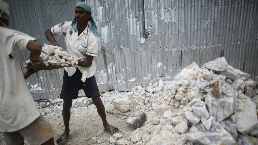 A worker helps his colleague to lift a bucket of limestone as they work in a stone crushing factory at Burimari in Lalmonirhat district. According to a report by the Bangladesh Institute of Labor Studies, those working in the industry run the risk of contracting silicosis, an incurable lung disease caused by inhalation of silica dust.