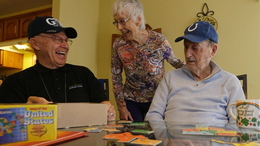 Caregiver Warren Manchess with Paul Gregoline and Paul's wife, Mary, as they work on a puzzle, in Noblesville, Ind.