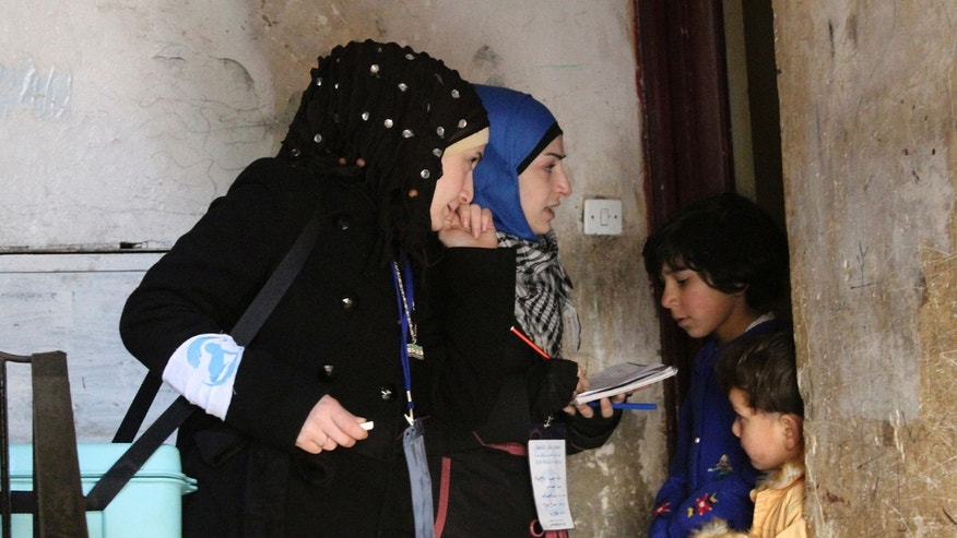 Activist health workers speak to family members before administering polio vaccinations in Aleppo January 5, 2014. (REUTERS/Hosam Katan)