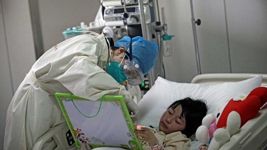 A girl infected with the new H7N9 bird flu strain draws a picture with a nurse at Ditan Hospital in Beijing, April 14, 2013. (REUTERS/Suzie Wong)