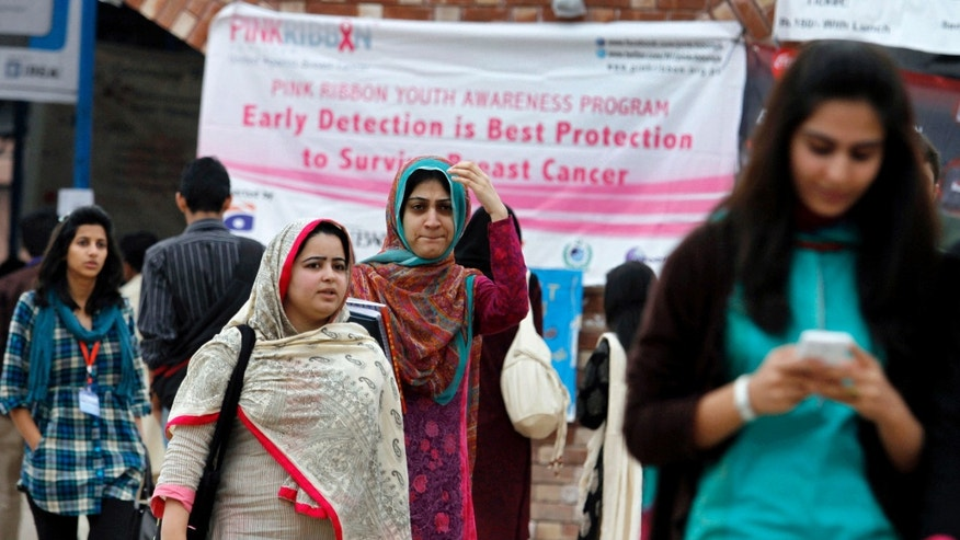 Students walk past a banner promoting awareness on breast cancer at a university in Islamabad, Pakistan. (AP Photo/Anjum Naveed)