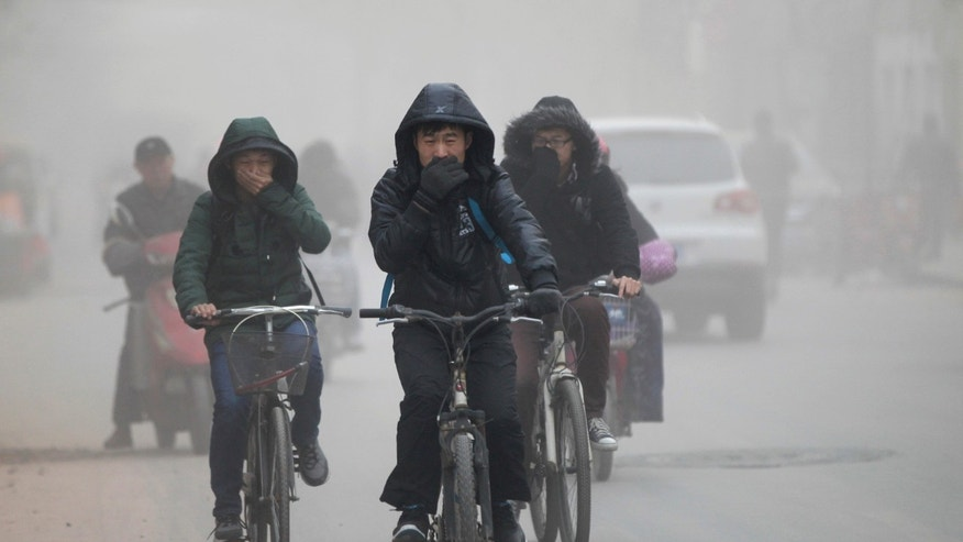 Residents cover their face from dust as they ride their bicycles along a street on a hazy day in Zhengzhou, Henan province China on December 10, 2013. (REUTERS/Stringer)
