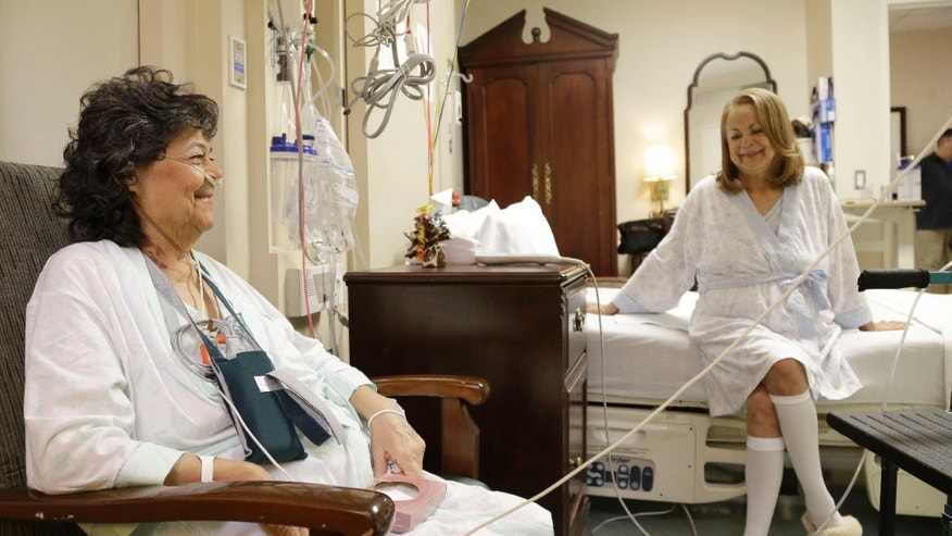 Irma Myers-Santana, left, and her sister Anna Williamson visit in Williamson's hospital room in Houston. Earlier this month the sisters ended up in the same operating room, each getting one lung from the same donor. (AP Photo/Pat Sullivan)