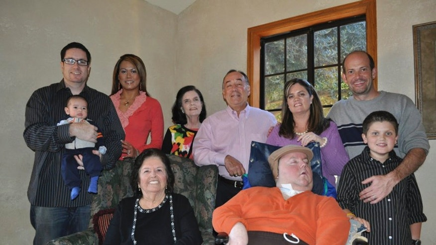Mikey Cortez, front row, center, and his family members on Thanksgiving Day. (AP Photo/Courtesy Cortez Family)