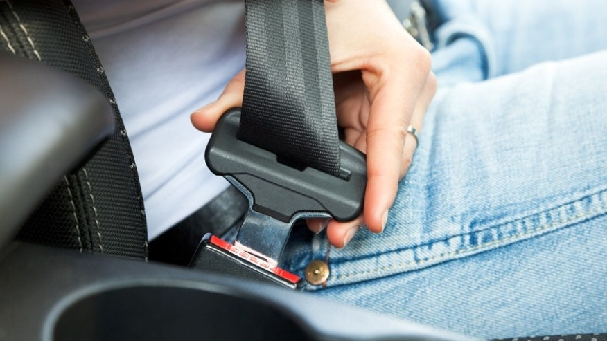 close up of female fastening safety belt in car