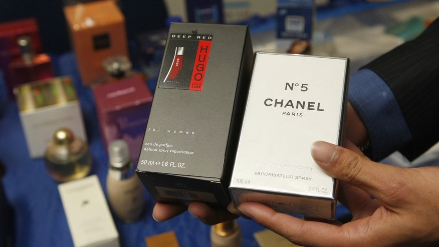 A man shows fake perfumes at the start of the High Level Conference on Counterfeiting and Piracy in Brussels.