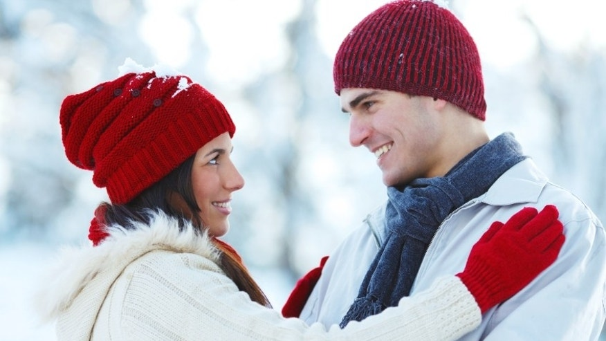 Beautiful young couple wearing red knit hats. They are looking at each other. 