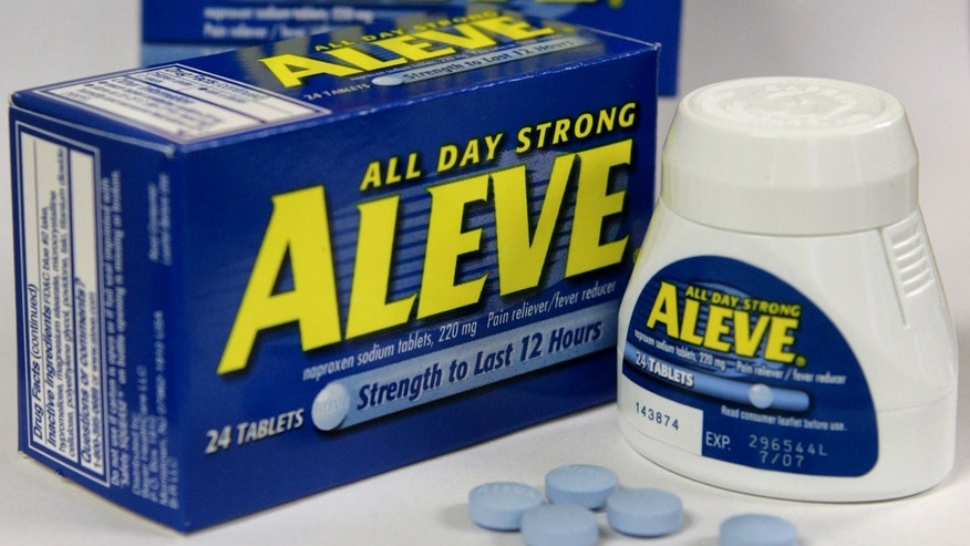 Several Aleve tablets appear in front of bottles of the pain reliever. (AP Photo/Steven Senne, File)