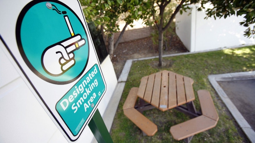 A sign marking a designated smoking area stands behind the city hall of Calabasas, California. The city banned smoking in all public areas including parks and sidewalks in 2006. (Reuters)
