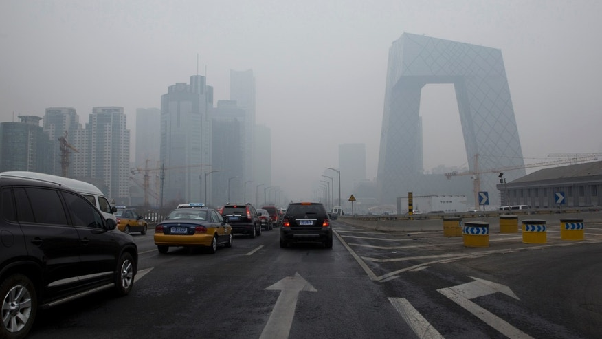Cars clog in the traffic in Beijing's Central Business District on a hazy day, Friday, Feb. 21, 2014. (AP Photo/Alexander F. Yuan)
