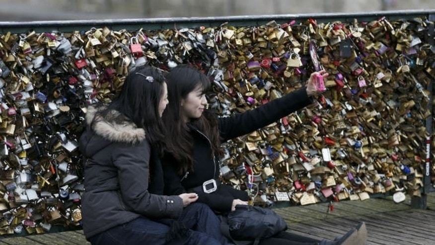 """Tourists make a """"selfie"""" picture in front of padlocks clipped by lovers on the Pont des Arts over the River Seine in Paris (REUTERS/Charles Platiau)"""