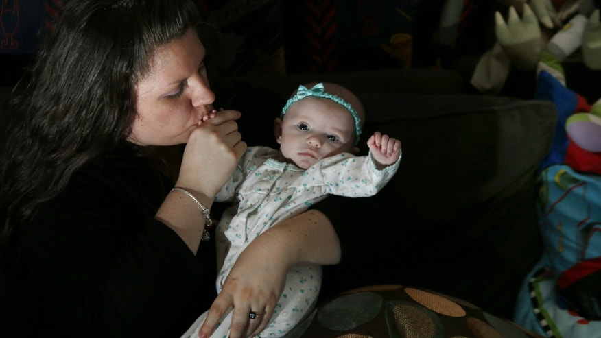 Jennifer Fontaine kisses her baby daughter, Morgan, at her parents' home in Methuen, Mass. After Fontaine's standard prenatal screening suggested her fetus might have Edwards syndrome, a doctor suggested a fetal DNA test, which suggested her fetus was fine.