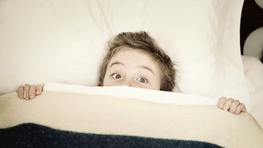 Boy hiding in bed.