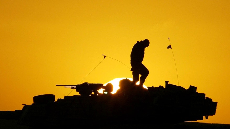 FILE - A U.S. soldier walks atop his armored vehicle at sunset as he prepares for a nighttime military exercise in the Kuwaiti desert south of the Iraqi border on Sunday, Dec. 22, 2002. Combat appears to have little or no influence on suicide rates among U.S. troops and veterans, according to a military study that challenges the conventional thinking about war�s effects on the psyche published Tuesday, Aug. 6, 2013 in the Journal of the American Medical Association. (AP Photo/Anja Niedringhaus)
