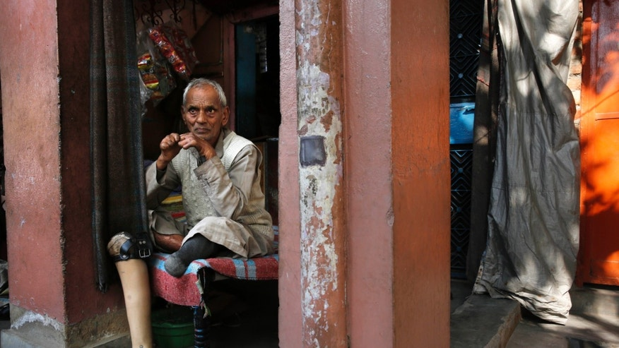 Leprosy patient Satnarayan Singh, 86, sits outside his shop at a leper colony in New Delhi, India. (AP Photo/Manish Swarup)